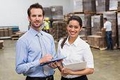 stock photo of warehouse  - Smiling warehouse managers working together in a large warehouse - JPG
