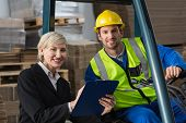 foto of forklift driver  - Forklift driver and manager smiling at camera in a large warehouse - JPG