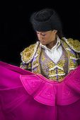 picture of bullfighting  - Woman bullfighter holding capote pink on black background - JPG