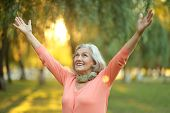 stock photo of senior adult  - Senior woman walking in the park in autumn - JPG
