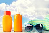 stock photo of dispenser  - Bottles of suntan cream with sunglasses and hat on table isolated on white - JPG