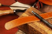 foto of leather tool  - Craft tools with leather belt on table close up - JPG