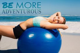 foto of generous  - Fit woman lying on exercise ball at the beach stretching against be more generous - JPG