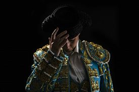 stock photo of bullfighting  - Woman bullfighter salutes with his montera in black background - JPG