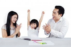 stock photo of applause  - Joyful little girl raise her hands after finishing her schools assignment and get applause - JPG