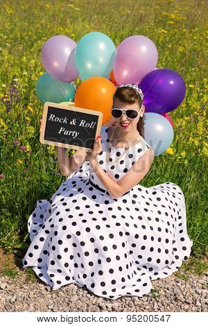 Pinup Girl With Balloons In The Nature Holding A Slate With Text Rock & Roll Party