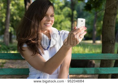 Young Happy Smiling Woman Sitting On A Park Bench In The Shade Of The Trees And Makes A Selfie On He