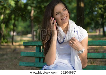 Young Smiling Woman Talking On The Phone On A Park Bench