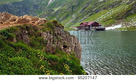 Idyllic View With Cottege On Balea Lake Shore In Fagaras Mountains