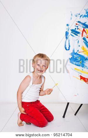 Little kid painting paints picture on easel. Education. Creativity. Studio portrait over white backg