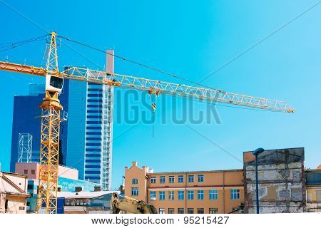 Construction Crane On Background Of New Modern Skyscraper And Ol