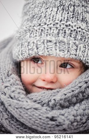 close up outdoor winter vertical portrait of adorable happy baby girl in grey knitted hat and scarf