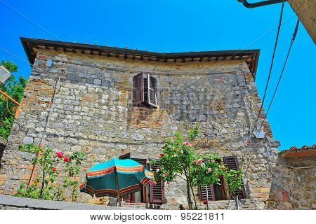 Umbrella And Flowers In Front Of A Rustic Building In San Gimignano