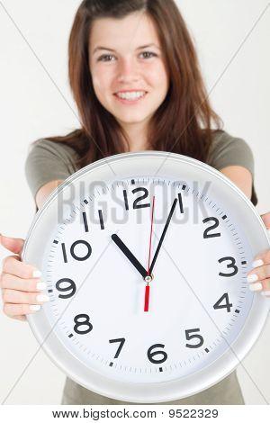 pretty teen girl holding wall clock