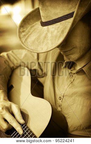 Man Playing Guitar In Western Hat