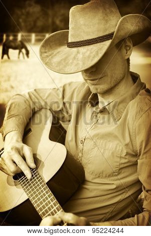 Handsome Cowboy In Western Hat Playing Guitar
