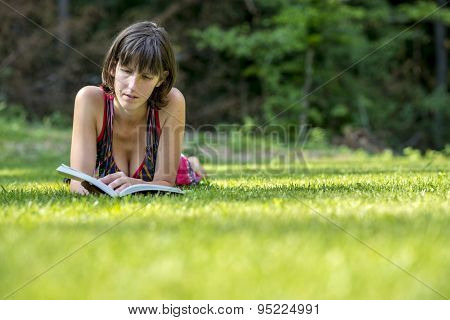 Woman Lying On The Grass While Reading A Book