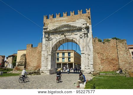 People pass under Augustus Arch - the ancient romanesque gate and the historical landmark of Rimini.