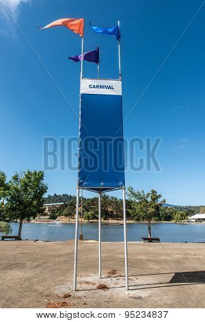 Carnival Sign With Three Flags By Lake