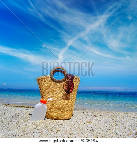 Straw Bag And Suntan Lotion Bottle Under A Cloudy Sky