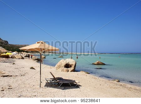 Beach umbrella and sunbed on the background of the blue sea