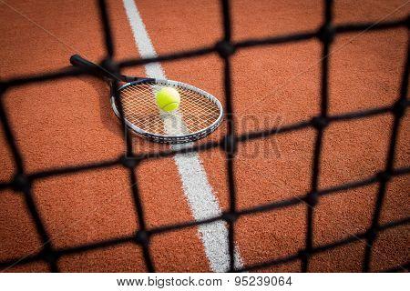 Tennis Racket And Ball On Court Through Net
