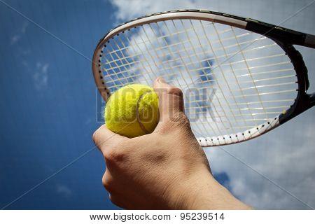 Hand Holding Tennis Ball And Racket Agaist Sky