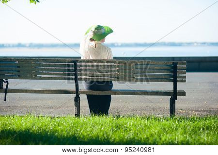 Woman In Old-fashioned Dress Sitting On The Bench
