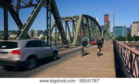 Cyclists  And Cars Cross The Hawthorne Bridge Into Portland, Oregon