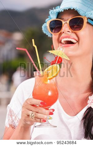 Happy young woman drinking cocktail