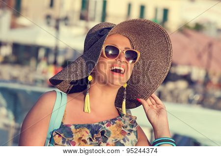 Happy woman with big straw hat walking at sunset