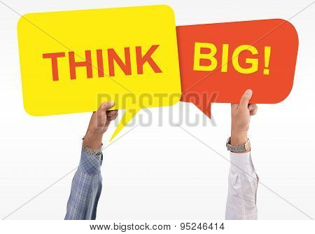 Two speech bubbles in hand with the word think big mentioned