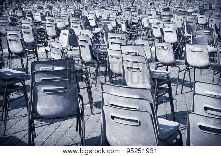 Multitude Of Empty Chair On Road Pavement