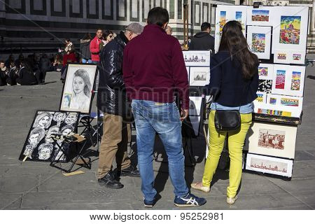 Tourists Looking At Paintings Near Florence Cathedral In Italy