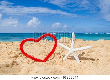 Starfish With Heart Shape On The Sandy Beach