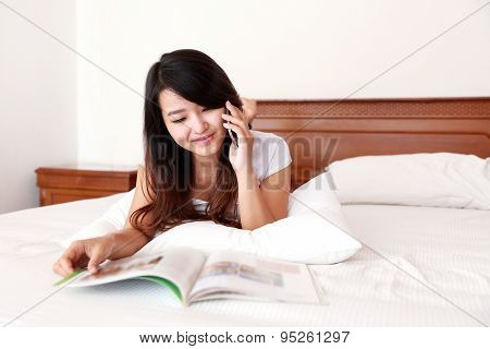 Young Woman Enjoy Reading A Magazine While Talking On The Mobilephone