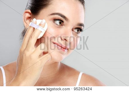Beautiful Woman Smiling While Applying Some Powder Using Powder Puff