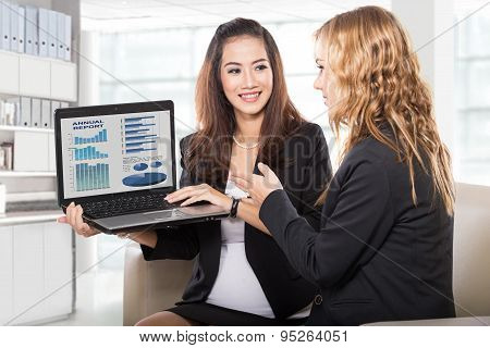 Two Friendly Businesswomen Sitting And Discussing New Ideas Using Laptop Computer