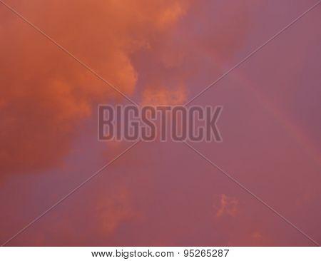 fiery cloudy sky with slight rainbow