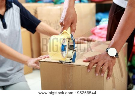 Worker Using Duck Tape For Packing Product Into A Box