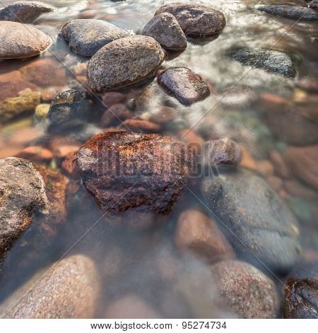 Rocks In A Fast Flowing Crystal Clear Stream