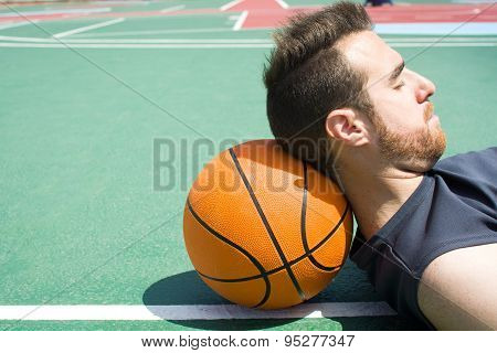 man lying on the basketball field