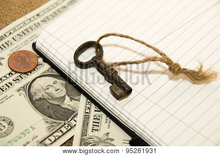 Opened Notebook, Key And Money On The Old Tissue