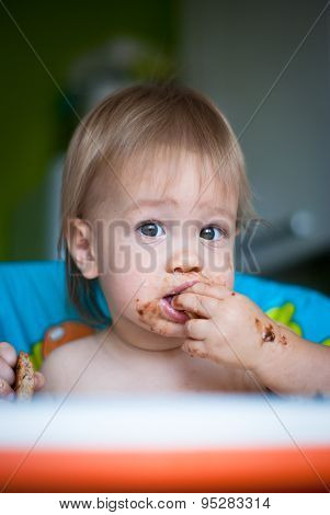 Child eats cake in the highchair