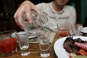 image of vodka  - Man pouring vodka from a carafe in the pub - JPG