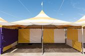 foto of canopy  - Canopy tent set up outdoors with flag on top is empty - JPG