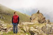 picture of italian alps  - Female hiker reaching her goal at the mountain top and looking above in a cloudy and foggy day - JPG