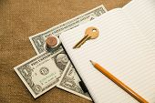 foto of memento  - Opened notebook with a blank sheet pencil key and money on the old tissue - JPG