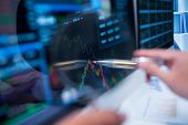 picture of touching  - Touching stock market graph on a touch screen device - JPG