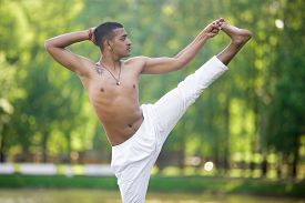stock photo of ashtanga vinyasa yoga  - Portrait of attractive Indian young man in white linen clothes practicing yoga fitness pilates on pond in park standing in Extended Hand to Big Toe yoga pose Utthita Hasta Padangustasana - JPG